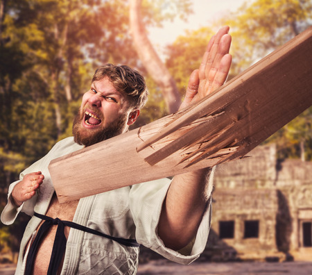 artes marciales: Fuerte karateka rompe tablón de madera a mano