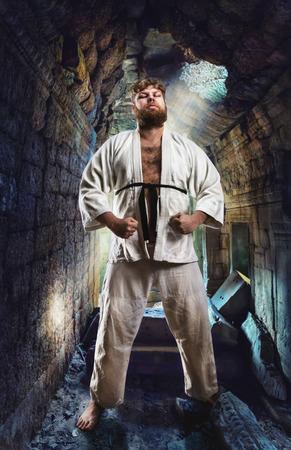 sensei: Serious karate fighter in white kimono in the temple hall