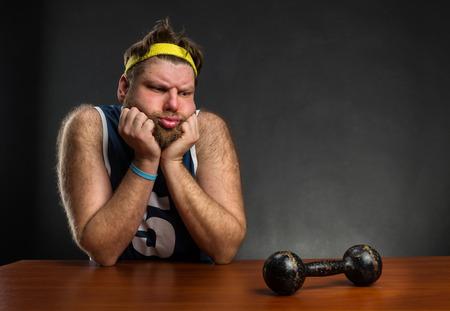 morose: Sad man looking at dumbbell at the table