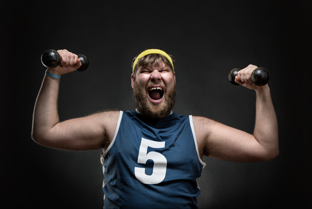 Happy smiling man with dumbbells in his both hands over grey Stock Photo