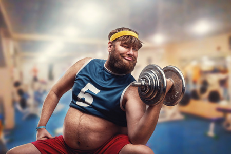 gimnasia: Hombre gordo hacer ejercicios con una pesa en el gimnasio