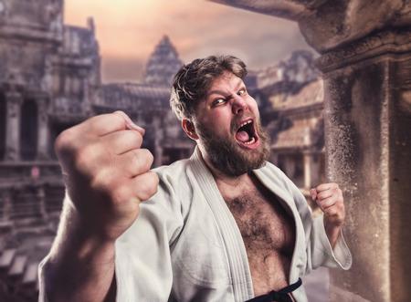 sensei: Aggressive bearded karate fighter in white kimono in the temple