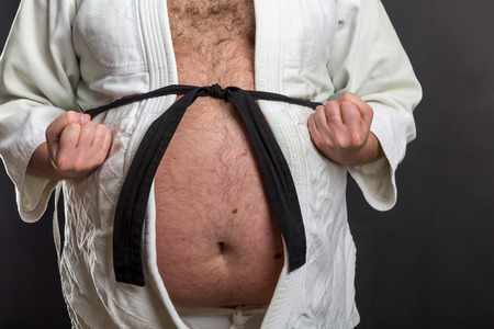 Closeup of fat karate fighter belly in white kimono with black belt Stock Photo
