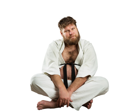 black belt: Fat karate fighter sits with crossed legs over white Stock Photo
