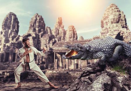 흰색 기모노 가라테 카는 거대한 악어와 싸움