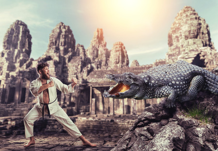 animal fight: Karateka in white kimono fights with giant alligator Stock Photo