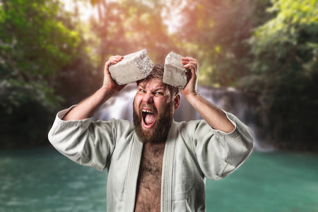 black belt: Strong karateka breaks a brick on his head Stock Photo