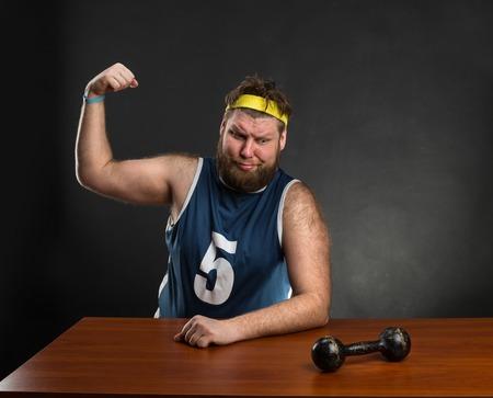 hombre fuerte: Hombre gordo muestra su músculo con una mancuerna en la mesa