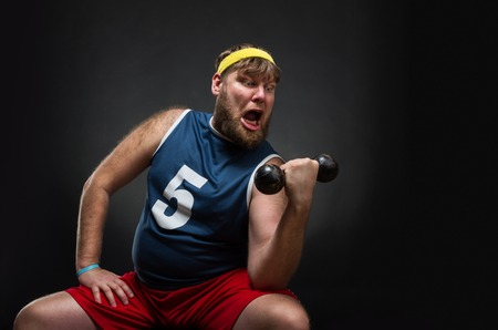 Fat man do exercise with a dumbbell over grey