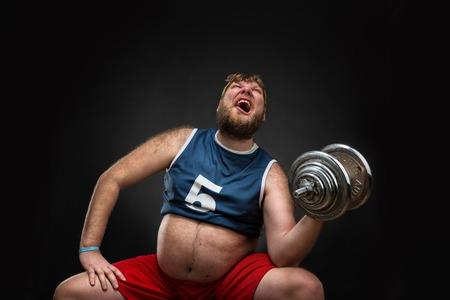 グレーの上のダンベルのデブ男はハードな運動