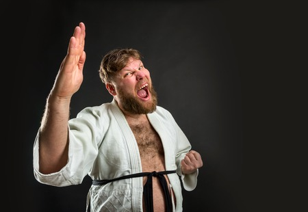 karate fighter: Mad bearded strong karate fighter in white kimono over grey