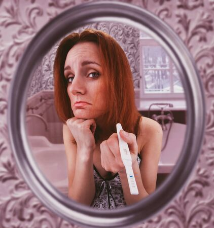 deplorable: Sad woman looks in the mirror showing her pregnancy test