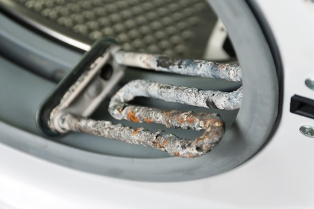 limescale: Washing machine and damaged electric heater with limescale