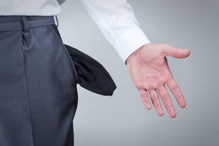 empty pockets: Businessman pulling out empty pockets over gray background Stock Photo