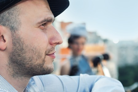 male face: Profile of young bearded man in a cap