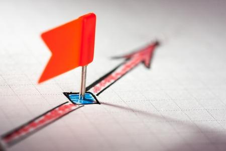planificacion: Un pin en la flecha roja dibujada en el papel