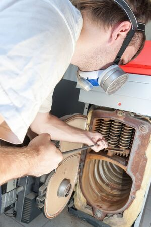 Close up of  gas-man cleaning big gas boiler photo