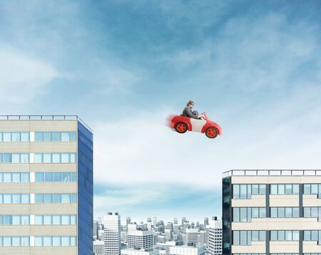 strange: Young businessman driving car jumping between two high buildings