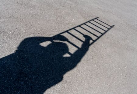 climbing ladder: Shadow of man climbing ladder on asphalt Stock Photo