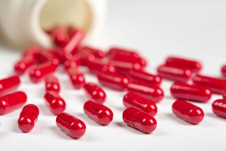 packs of pills: Close up of red pills scattered on the table Stock Photo
