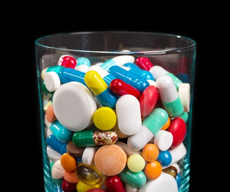 differnt: Close up of heap of many differnt pills in glass