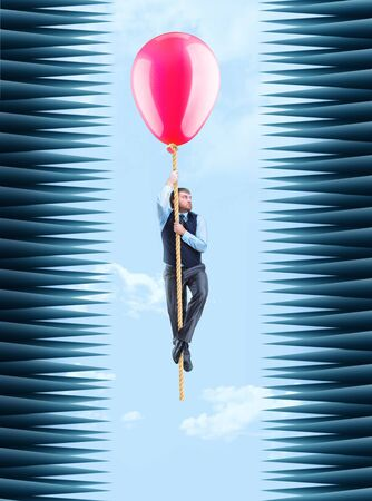 thorny: Businessman hanging on the rope with a big ballon in a thorny tunnel Stock Photo