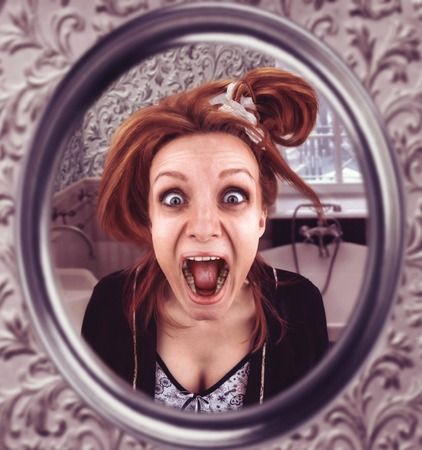 bawl: Scared woman looks in th mirror screaming