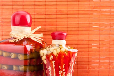 a jar stand: Two jars of pickled haricot and other vegetables over red background Stock Photo