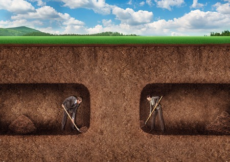 tunneling: Businessman and businesswoman dig a tunnel underground towards each other Stock Photo