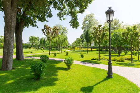modern garden: Beautiful spring green park with stone pavements and street lamp Stock Photo