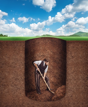 Businessman digs a tunnel deep into the ground
