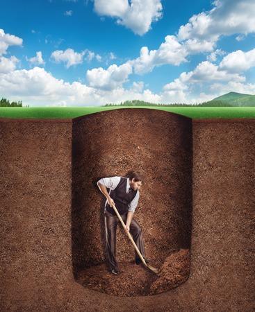 terreno: Uomo d'affari che scava un tunnel in profondità nel terreno Archivio Fotografico
