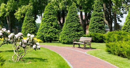 park bench: Bench in the park and curved stone brick path Stock Photo