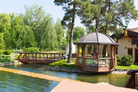 summerhouse: Beautiful pond in spring park with wooden summer-house
