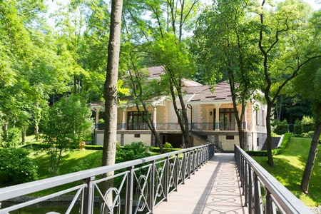 sumptuousness: View of modern house in the park from bridge Stock Photo