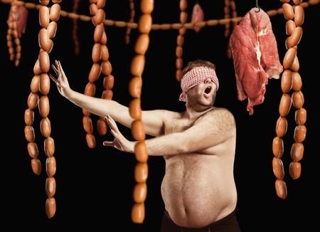 starvation: Fat man blindfolded looking for sausages over black background