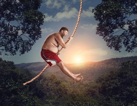 aventura: Salvaje feliz volando en el aire por la cuerda en el bosque por la noche Foto de archivo