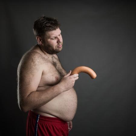 pene: Vista lateral del hombre gordo con una salchicha en la mano. Problema Potencia Foto de archivo