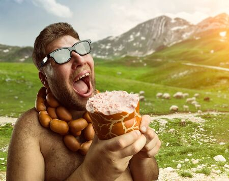 unhealthy diet: Hungry man with sausages round his neck eats one more sausage in the mountains