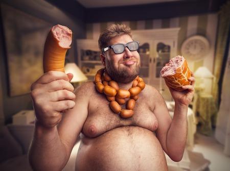 obesidad: Hombre feliz en gafas con salchichas redondas del cuello tiene grandes salchichas, tanto en la mano, sentado en la sala de Foto de archivo