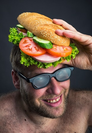 dirty man: Happy man in glasses holding sandwich on his head