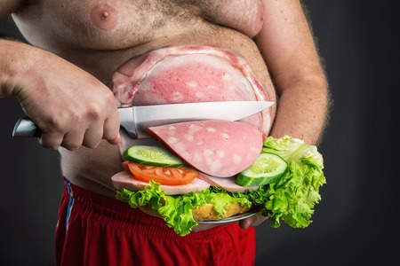 make dirty: Fat man cutting a sausage slice for sandwich from his belly