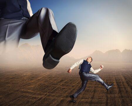 odd jobs: Businessman runs in a desert from a big foot