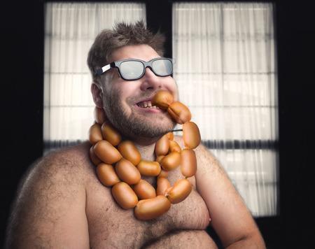 Happy homme barbu manger des saucisses de son cou Banque d'images