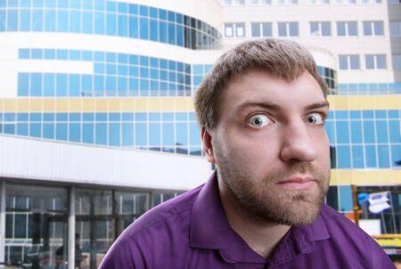 behalf: Strange bearded adult man looks at you over building background
