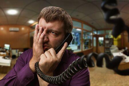 llamando: Frustrado hombre con barba habla por teléfono en la oficina Foto de archivo