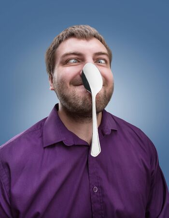 Strange adult man holds a spoon on his nose Stock Photo