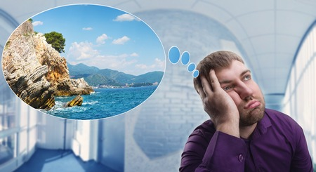 soñando: Hombre triste soñando con sus vacaciones de verano en el trabajo