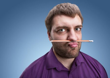 odd jobs: Strange bearded man holds pencil with his nose and lips