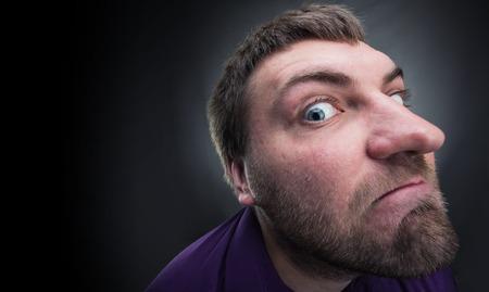 mistrust: Adult bearded inquisitive man over grey background